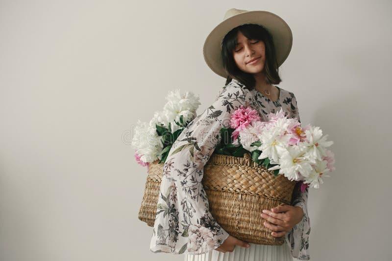 Sinnlig stående av bohoflickan som rymmer rosa och vita pioner i lantlig korg Stilfull hipsterkvinna i hatt och bohemiskt blom- arkivbild