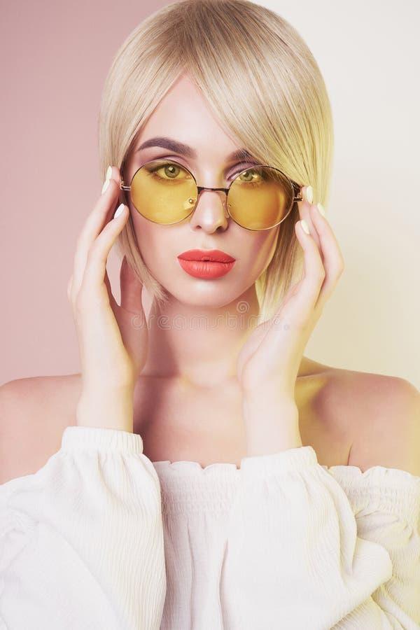 Sinnlig stilfull kvinna i erotisk vit kl?nning Bl??gd dam med perfekta kanter i modern f?rgsolglas?gon arkivfoton
