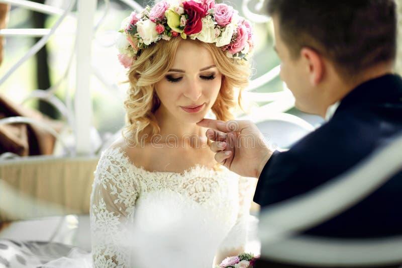 Sinnlig tryckande på emotionell lycklig blond brud för stilig brudgum in royaltyfri foto
