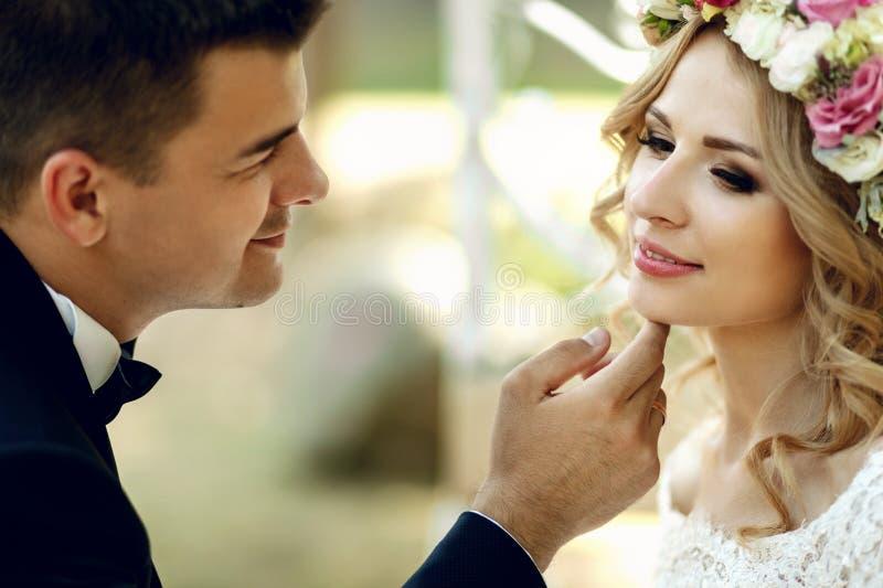 Sinnlig tryckande på emotionell lycklig blond brud för stilig brudgum in fotografering för bildbyråer