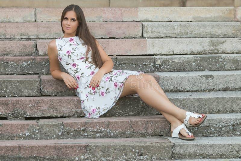 Sinnlig ung brunettkvinnastående som sitter utomhus på trappa royaltyfria bilder