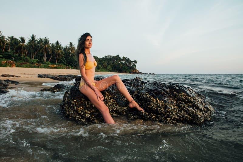 Sinnlig ung brunettskönhet som bär den gula baddräkten med härligt hårsammanträde på stenen på stranden royaltyfria bilder