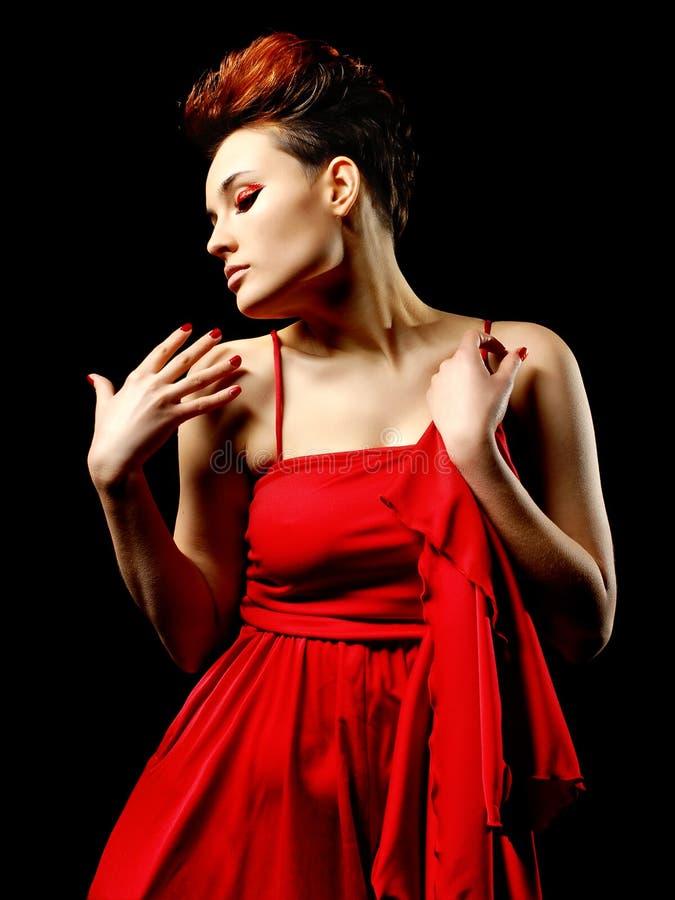 Sinnlig ung dam i den röda klänningen som poserar en studio kvinna för silhouette för symbol för skönhetbegreppsmode set arkivfoto