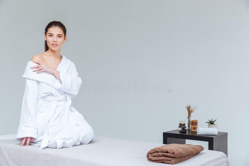Sinnlig ung kvinna i badrocksammanträde i brunnsortsalong royaltyfri fotografi
