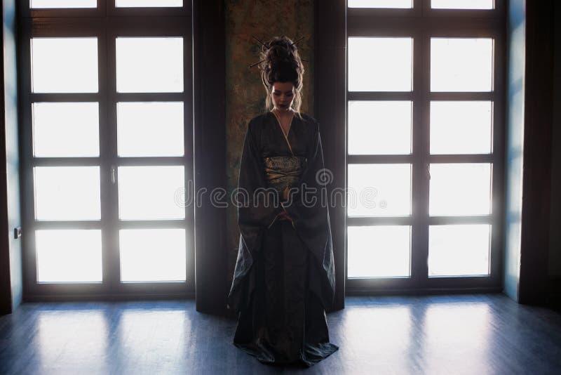 Sinnlig ung kvinna i en asiatisk dräkt för geisha med modemakeup och hårstil royaltyfria foton