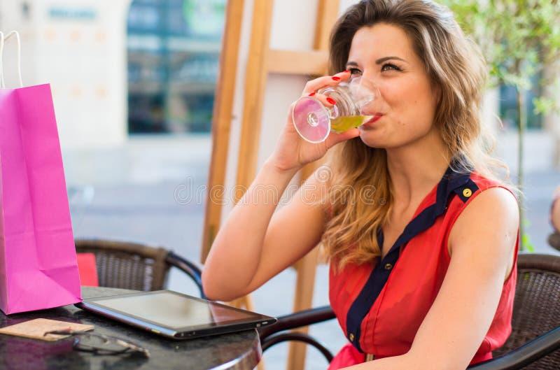 Sinnlig ung kvinna med drinksammanträde i ett kafé. arkivfoton