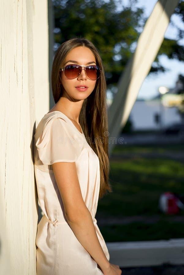 Sinnlig ung stilfull kvinna för utomhus- modeståendeglamour i exponeringsglas som bär en delikat brunett för sommarklänningdräkt arkivbild