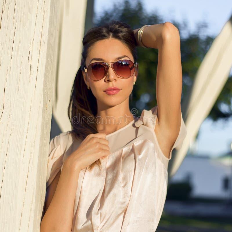Sinnlig ung stilfull kvinna för utomhus- modeståendeglamour i exponeringsglas som bär en delikat brunett för sommarklänningdräkt royaltyfria bilder