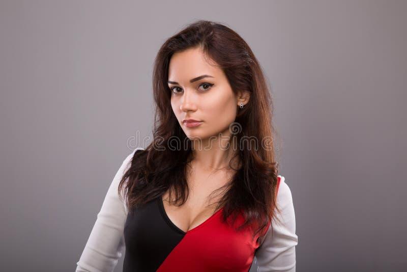 Sinnlig ursnygg kvinna med förförisk blick på kameran Stående över grå studiobakgrund royaltyfri foto