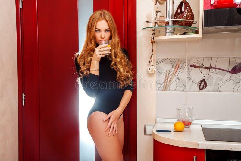 Sinnlig vuxen kvinnlig med coctailen i kök arkivbild