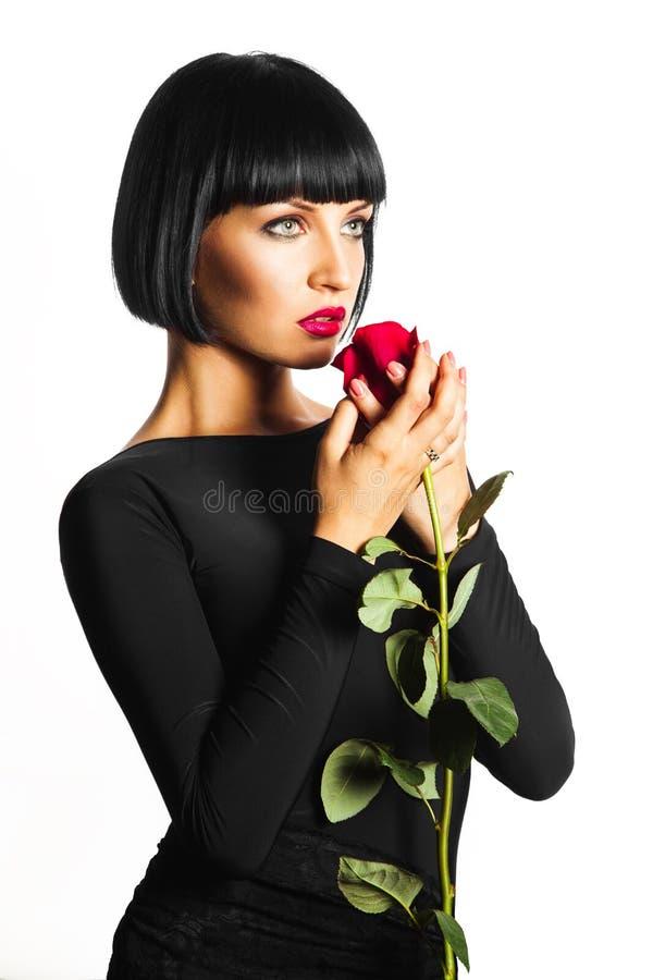 Sinnlig vuxen kvinnlig med den röda rosen på vit bakgrund royaltyfri bild