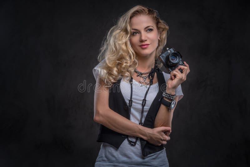 Sinnliga lockiga blonda den iklädda flickafotografen en vit t-skjorta och waistcoat bär mycket tillbehör och fotografering för bildbyråer