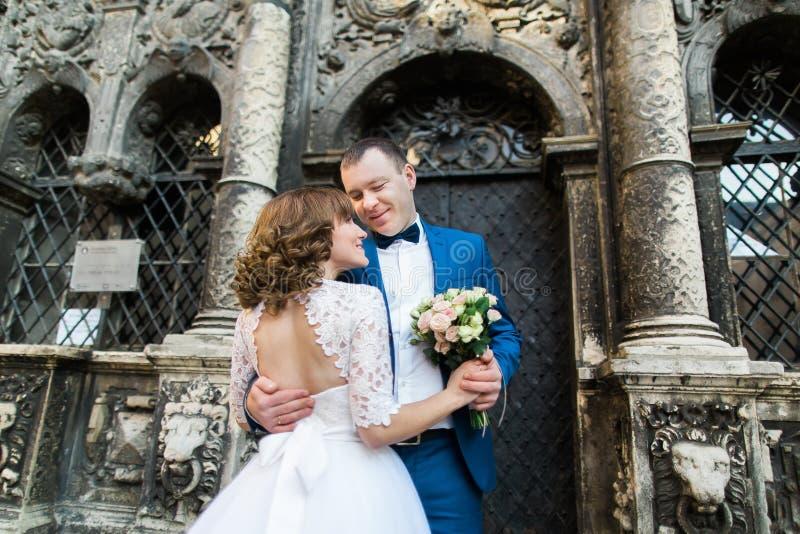 Sinnliga nygift personpar som kramar nära gammal byggnad med kolonner arkivbild