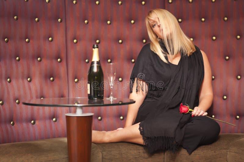 Sinnligt blont kvinnasammanträde nära champagne och ro arkivbild