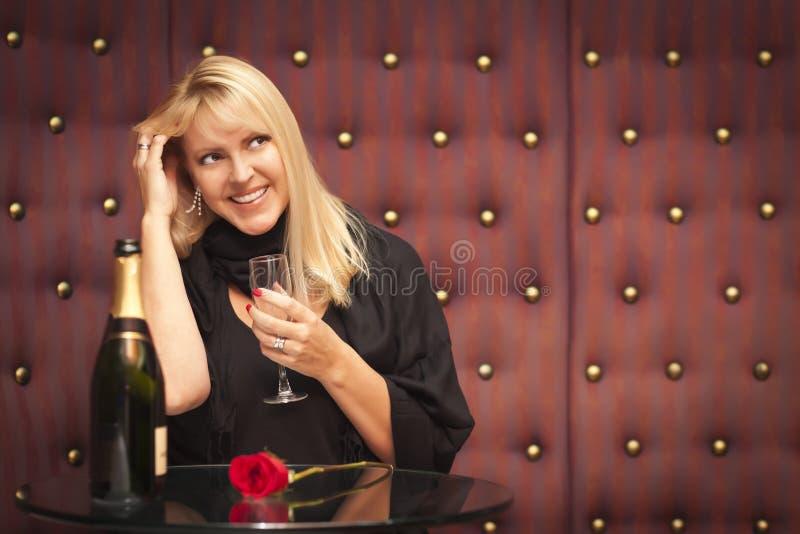 Sinnligt blont kvinnasammanträde nära champagne och ro royaltyfria foton