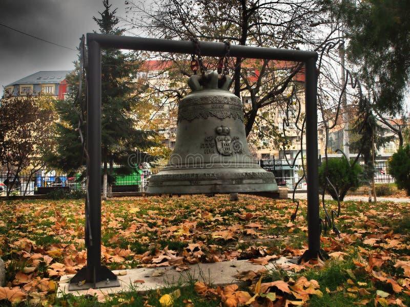 Sino de ferro velho no parque em frente à igreja Saint George New Church, em Bucareste, Romênia fotografia de stock