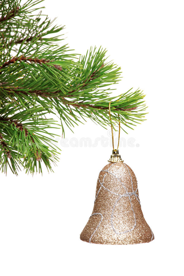 Sino do ouro que pendura em uma filial de árvore verde do Natal imagens de stock