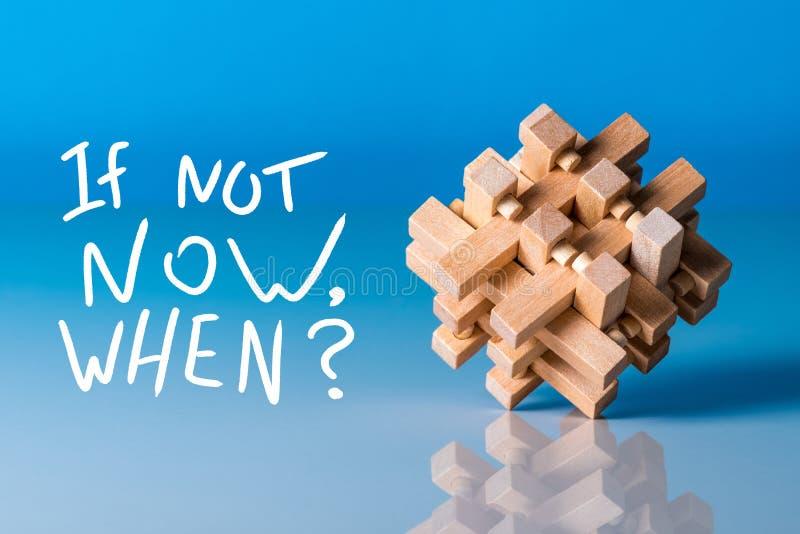 Sinon maintenant, quand - question au fond bleu avec l'énigme en bois photos stock