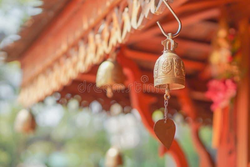 Sinos dourados pequenos que penduram sob o telhado fotografia de stock royalty free