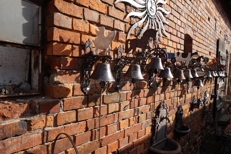 Sinos feitos a mão colocados na parede de tijolo da casa foto de stock