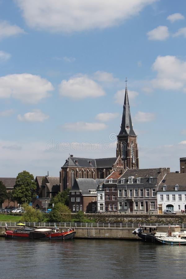Sint-Martinuskerk Maastricht nos bancos do Mosa Riveron, Maastricht, Países Baixos Paredes de tijolo de uma igreja histórica imagem de stock royalty free