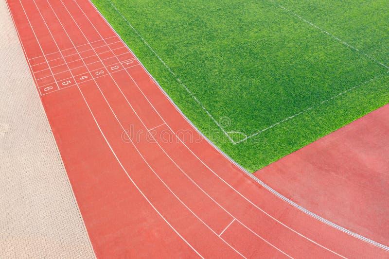 Sintelspoor op atletisch stadion en voetbalgebied met kunstmatig gras stock foto's