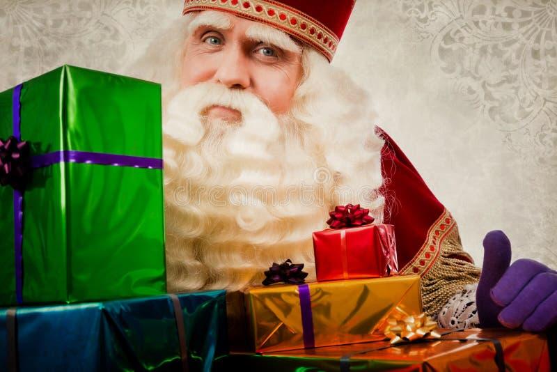Sinterklaas oder Sankt Nikolaus, die Geschenke zeigen lizenzfreie stockbilder