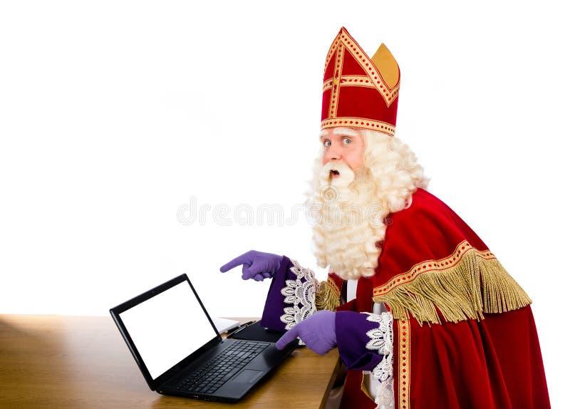 Sinterklaas oder Sankt Nikolaus mit Laptop lizenzfreie stockbilder