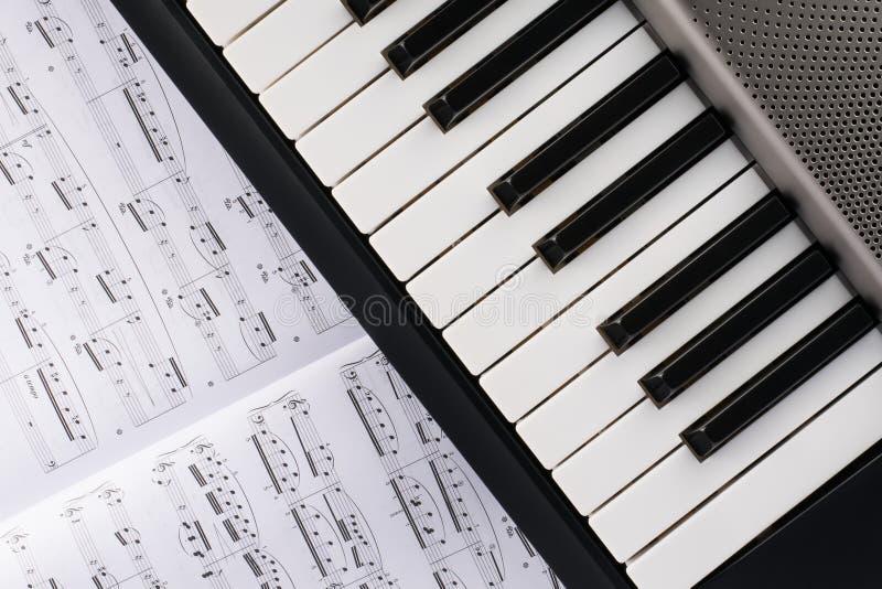 Sintetizador electr?nico del instrumento musical con la nota de la hoja fotos de archivo