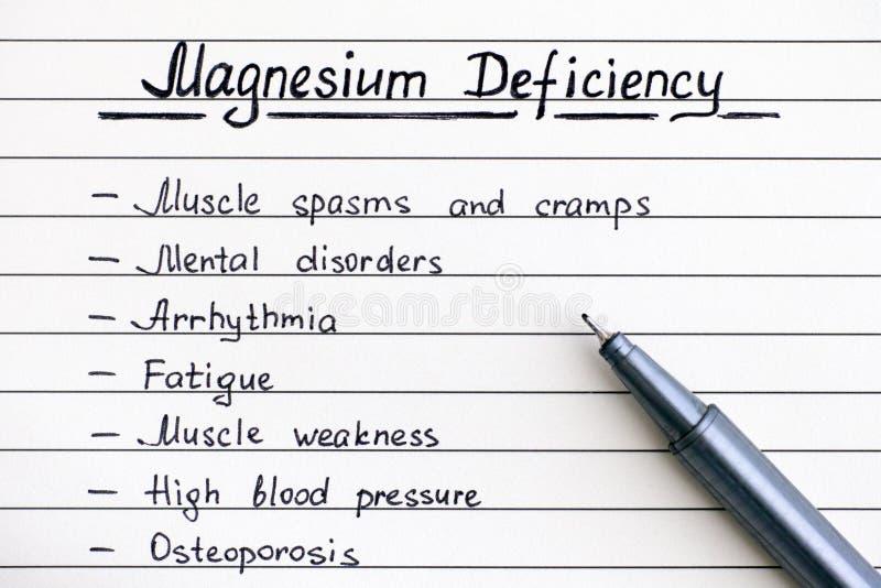Sintomas da escrita da deficiência do magnésio na lista com pena foto de stock