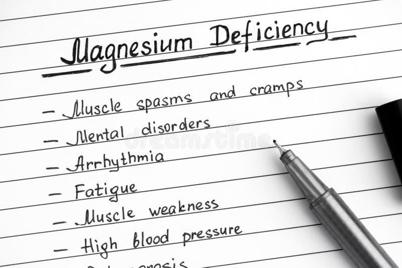 Sintomas da escrita da deficiência do magnésio na lista com pena preta imagem de stock royalty free