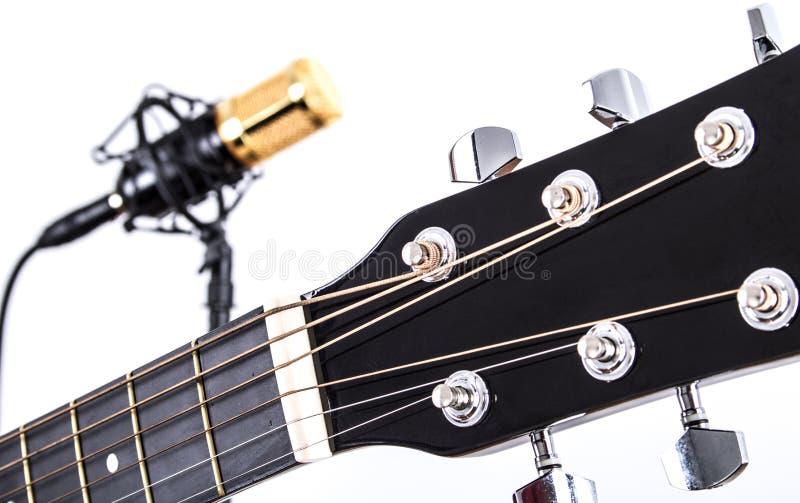 Sintonizzatori della chitarra acustica con il microfono a condensatore dell'oro nel fondo fotografia stock libera da diritti