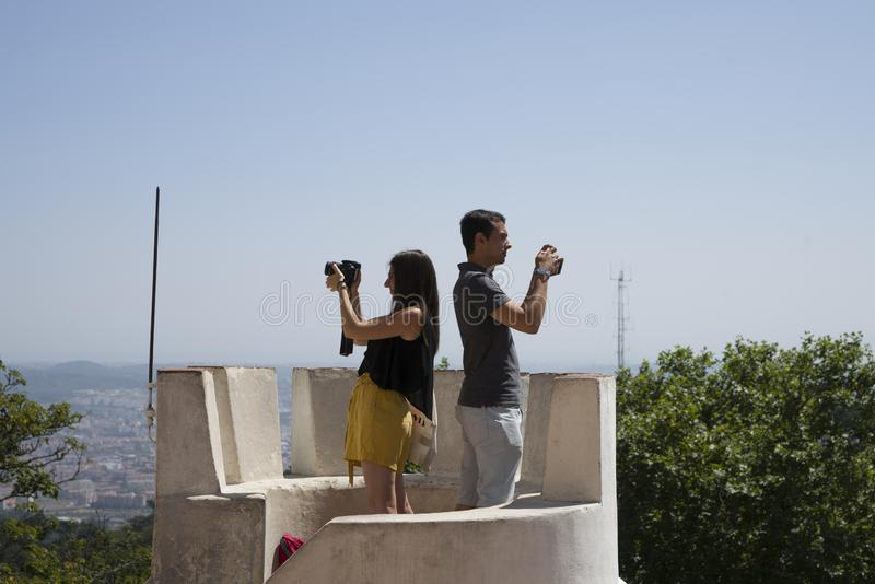 Sintra, Portugal, August 25, 2018: Young people take photos on the phone and camera from the tower. The girl and the young man royalty free stock photo