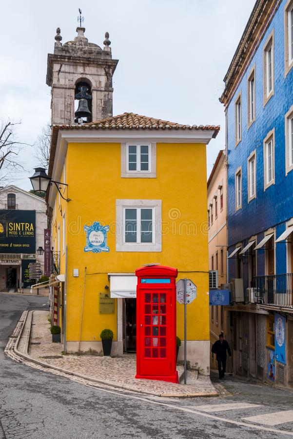 Phone booth. Sintra, Portugal - March 7, 2019 : Red phone booth in contrast with yellow building at Sintra, Portugal stock photos