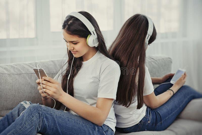 Siostr nastoletnie dziewczyny z słucha muzykę, ommunicate w ogólnospołecznych sieciach i zdjęcia royalty free