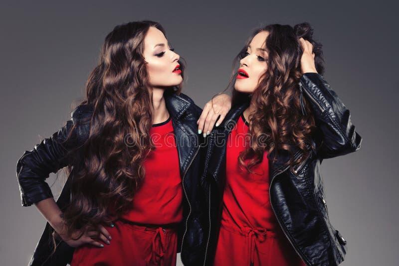 Siostra bliźniacy w modnisia stylu śmiać się moda modeluje dwa Wom zdjęcie stock
