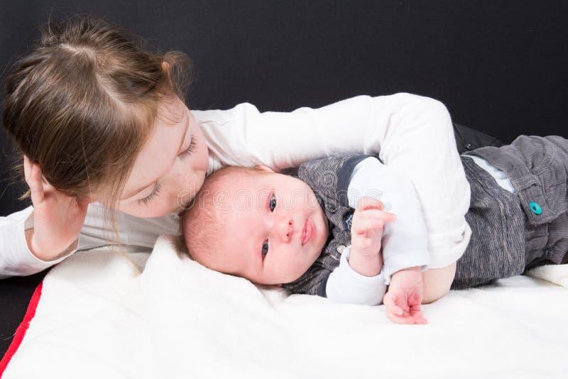 Siostra całuje jego młodszego brata dziecka berbecia dziewczyny nowonarodzonej chłopiec w pojęciu życie rodzinne i zdjęcie royalty free