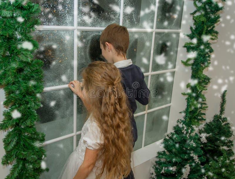 Siostra i brat w zimy pracownianym patrzeje śnieżnym okno fotografia royalty free