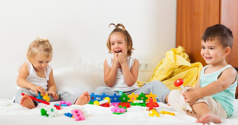 Siostry i brat ma zabawę w łóżku zdjęcie stock