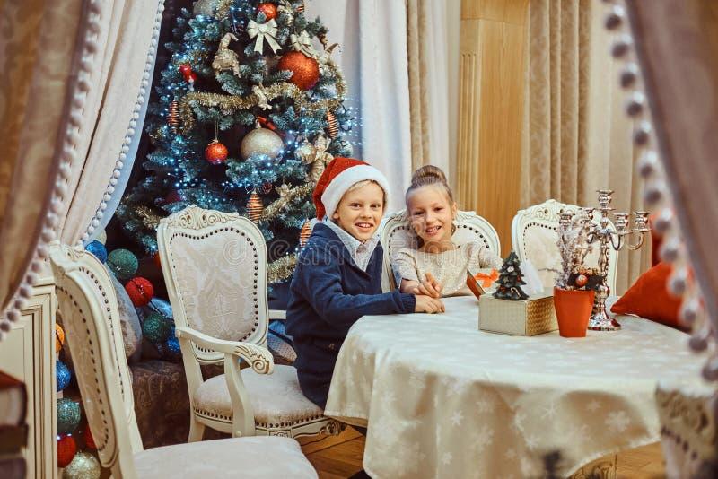 Siostry i brata obsiadanie przy stołem w eleganckim żywym pokoju dekorował dla bożych narodzeń fotografia stock