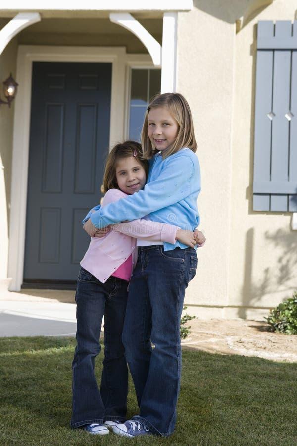 Siostry Obejmuje Przed domem zdjęcie royalty free
