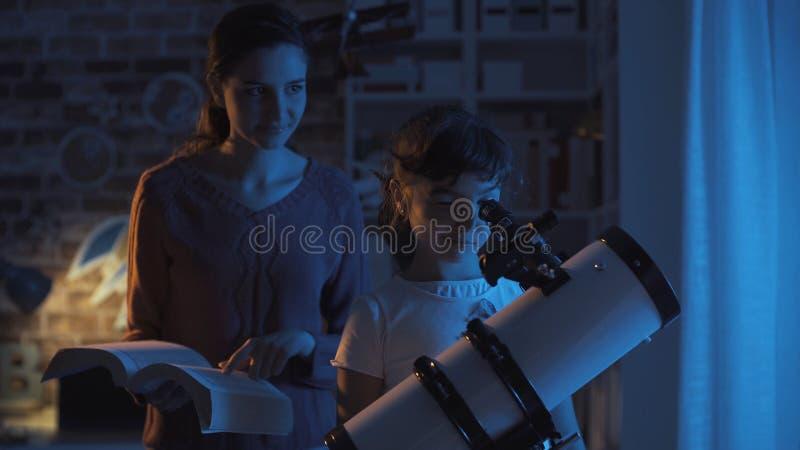 Siostry ogl?da gwiazdy astromony studiowa? i zdjęcie royalty free
