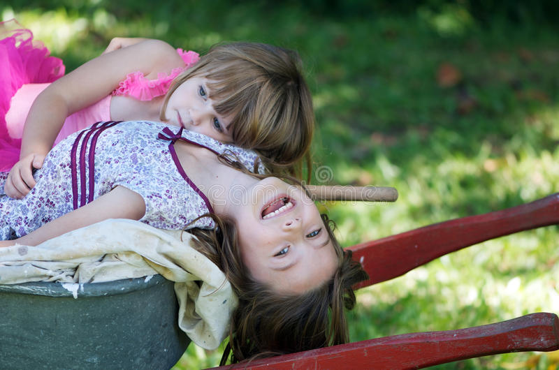 siostry wheelbarrow dwa zdjęcia royalty free