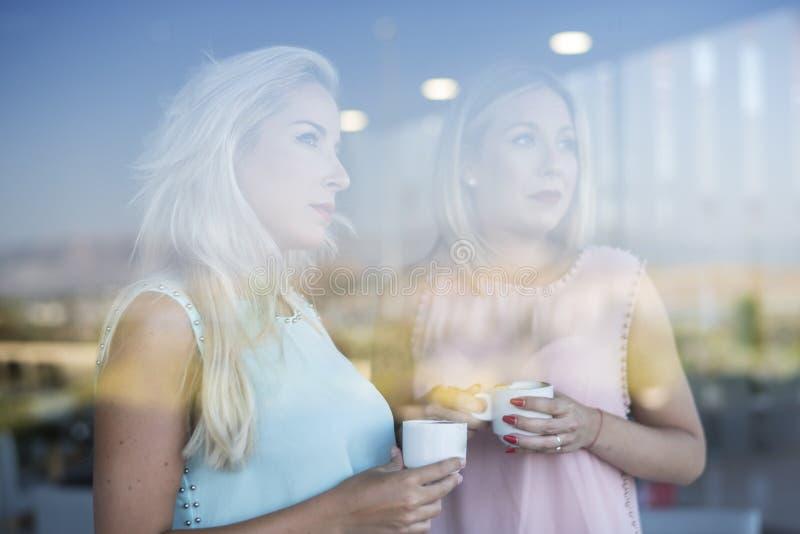 Siostrzana kobieta pije kawę w kawie za szkłem zdjęcia royalty free