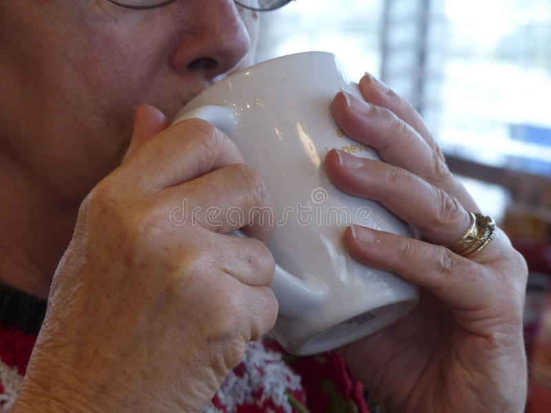 Woman Sipping Coffee. Looking out the window royalty free stock photography
