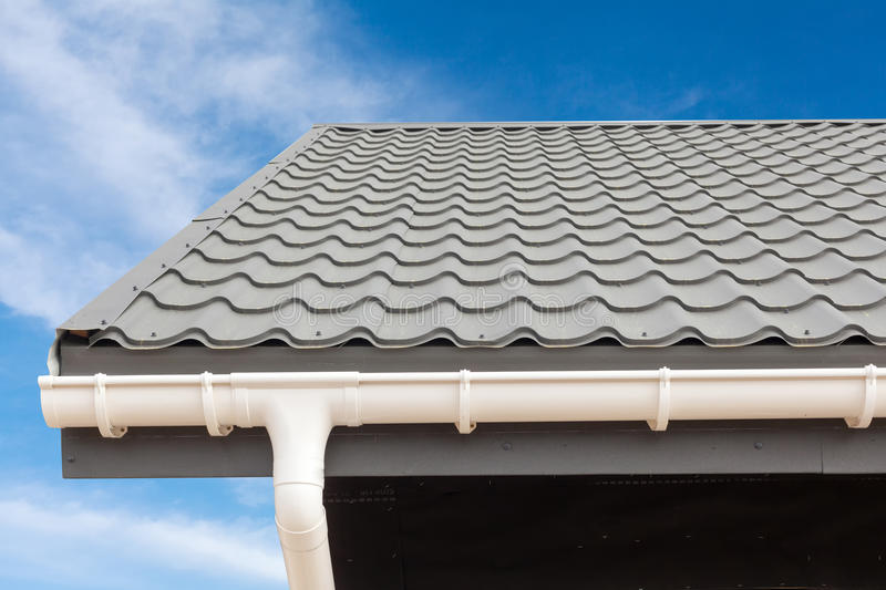 SIP panel house construction. New gray metal tile roof with white rain gutter. SIP panel house construction. New gray metal tile roof with white rain gutter royalty free stock image