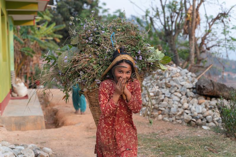Sipaghat/Nepal-28 07 2019: La muchacha del pequeño granjero con la cesta imagen de archivo libre de regalías