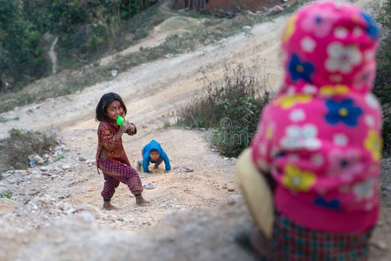 Sipaghat/Nepal-28 07 2019: Pequeños niños que resbalan abajo de la colina fotografía de archivo libre de regalías