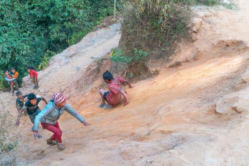 Sipaghat/Nepal-28 07 2019: Pequeños niños que resbalan abajo de la colina fotos de archivo