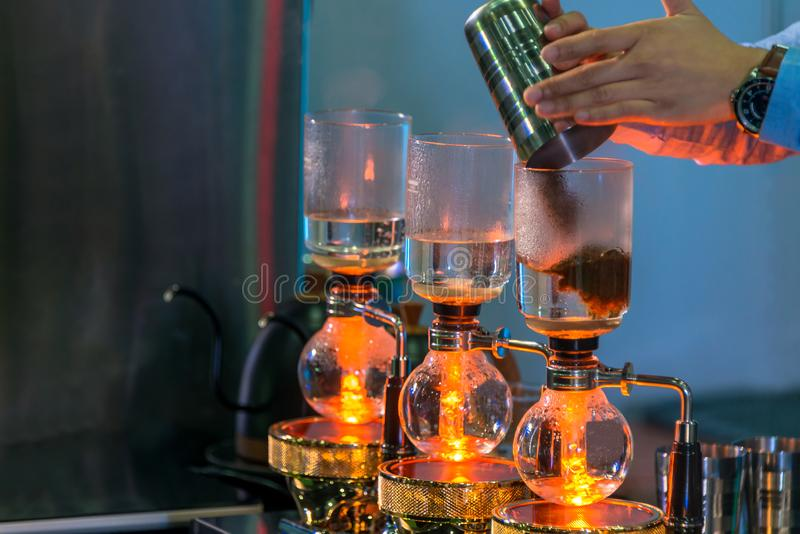 Siphon cacuum coffee maker grinder with drip brewing filtered coffee preparing in coffee shop stock images